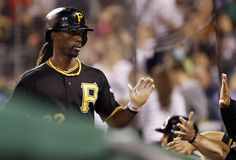 Andrew McCutchen #22 of the Pittsburgh Pirates is congratulated by teammates as he returns to the dugout after scoring on a sacrifice fly by Marlon Byrd #2 (not pictured) against the Cincinnati Reds during the sixth inning of their game on September 21, 2013 at PNC Park in Pittsburgh Pennsylvania. The Pirates defeated the Reds 4-2. (Photo by David Maxwell/Getty Images)