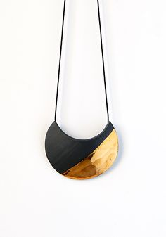 Crescent Necklace by Syra Gomez. Like sunlight passing across the moon's surface, 22K gold luster illuminates the eye-catching crescent form of this handcrafted black porcelain necklace. 28