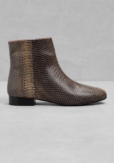 Clean-cut and understated, these everyday ankle boots feature a chunky zip fastening along the inner side and a reptile-like texture.
