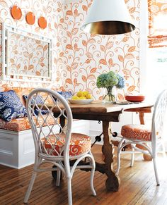 Fine orange scroll wallpaper compliments orange upholstered white dining wicker chairs for a quaint eat in kitchen.
