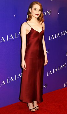 Emma Stone is wearing a wine color The Row slip dress. Emma never disappoints on the red carpet! I like her stylish style! The red dress and lip color pops really well with her red hair!