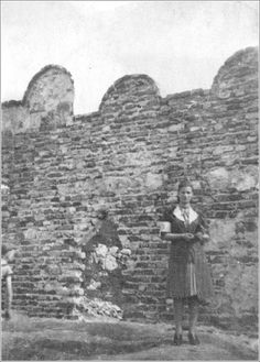 A Jewish girl stands next to the ghetto wall in Krakow