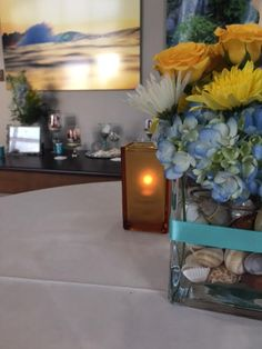 Worked with a florist to put seashells in the vases, adding a ribbon of her favorite color, and using yellow blue and white flowers which were her favorite colors