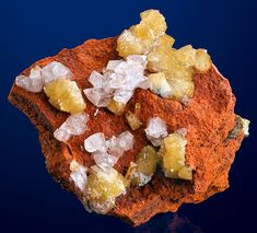 Glassy, isolated crystals of yellow Adamite with clear Calcites on Limonite matrix