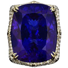 Untreated 78.78 Carat Tanzanite Ring. Weighing an astonishing 78.78 carats, this awe-inspiring natural Tanzanite dazzles with its incomparable and prized violet blue color. The jewel is formed in a cushion-shape with a modified brilliant cut. Set in its stunning platinum and 18K gold ring, this rare gemstone is accentuated by 2.80 carats of shimmering white diamonds.