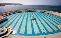 Tinside Pool on Plymouth Hoe is a renovated Grade II listed Art Deco Lido, and is reported to have been used as a landmark for German bombers. Visit Devon, Devon Uk, Devon England, Plymouth Hoe, Plymouth England, English Village, Worlds Of Fun, Outdoor Pool, Travel Posters