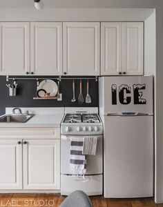 West Village NYC bachelor pad apartment kitchen featuring rental kitchen design decor ideas - removable ICE refrigerator decal, Ikea Grundtal drying rack, and chalkboard paint backsplash. Interior Design by LABLstudio.