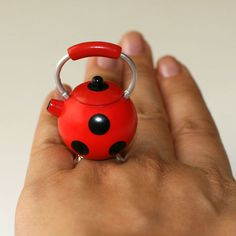 A super cute red teapot with black spots.....LadyBug Teapot!!!    It measures approx. 1.00 inch wide and 1.50 inch high is on a silver plated adjustable bang that will fit most ring sizes.