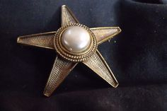 SOLD : A Vintage Hargo Creations Brooch signed HAR. This is a Gold Tone five point Star with a large Faux Pearl Center Piece produced in the late 1950s