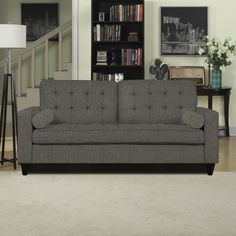 The Portfolio Home Furnishings Taya SoFast sofa features detailed lace tufted back cushions, track arms and a bench seat that can be assembled in less than 2 minutes. The sofa is covered in a charcoal gray linen fabric and includes two bolster pillows