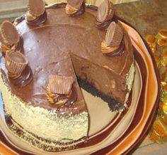 AMAZING EASY Reese's Peanut Butter Cup Cheesecake with brownie bottom and peanut butter cups mixed in!