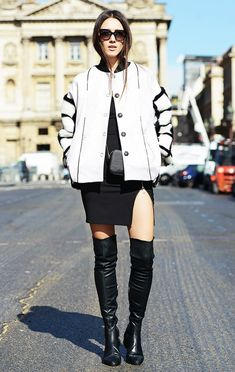 Diana Enciu wears a bomber jacket, slit dress, and over-the-knee boots