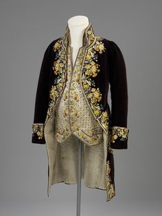 c1800 Court coat and waistcoat. Silk, cotton and chenille. This ensemble is typical of men's court dress at the end of the 18th century. Although the most formal style of dress worn, it was not the most fashionable. By 1800, rich fabrics and embroidery were no longer in style for men's suits. The standing collar, curving coat fronts and waistcoat style are also old fashioned, representing the cut and shape seen in the 1780s.  http://collections.vam.ac.uk/item/O137623/court-coat-and-unknown/#