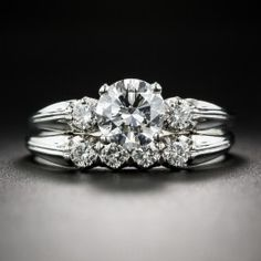 This classic mid-century platinum wedding set was created by the renowned San Francisco-based jeweler, Granat Brothers, who were known for their high quality die-struck mountings and attention to detail. The icy-white center diamond, graded by the GIA as E color - VS1 clarity, is framed on each side with a sparkling diamond set into a shank with fluted detail. The matching wedding band is set with a quartet of round diamonds. The set is currently sized 8 3/4.