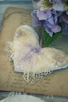 wonderful - i'm not sure of the materials, but I'm thinking a silky white lightly stuffed heart with a butterfly doily (or one shaped to form a butterfly) over the front, body embroidered on with purple thread, and embroidery attaching wings and forming markings - this is so pretty! - nelly vintage home: Сърчица- пеперуди