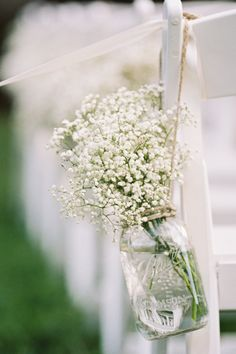 Whether hung with twine from aisle-facing ceremony chairs or clustered on dinner tables, Mason jars filled with wildflowers or baby's breath make the ultimate DIY wedding centerpieces.   - CountryLiving.com
