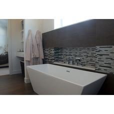 Modern contemporary home. Master bathroom, rectangle vessel tub, glass and metal mosaic tile, transom windows.