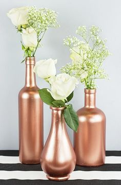 Wedding Decorations Rose Gold Wine Bottle Decor -- Dress up a table with fresh flowers and rose gold bottles. Gold Bottles, Painted Wine Bottles, Wine Bottle Centerpieces, Diy Centerpieces, Wine Bottle Decorations, White Centerpiece, White Vases, Bottle Painting, Bottle Art