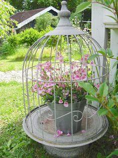 birdcage and flowers on pedestals