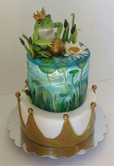 """Cake artist says, """"Frog prince first birthday cake. Hand painted top tier. Fondant crown on bottom tier, and hand made modeling chocolate cake topper"""""""