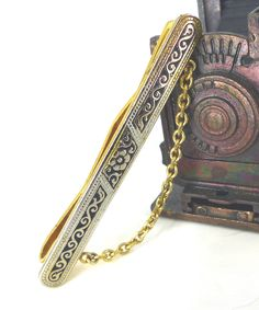 Gorgeous vintage floral damascene gold and black slip style tie bar with elegant chain. Incredible detail by ModernRenaissanceMan on Etsy https://www.etsy.com/listing/261976004/gorgeous-vintage-floral-damascene-gold