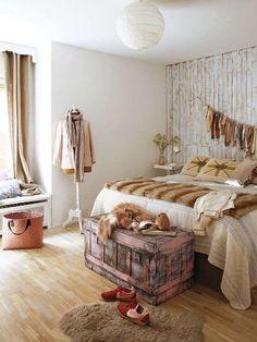 Dormitorio con papel pintado, suelo de parquet y aspecto vintage. Baúl antiguo a los pies.