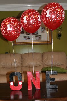 Mickey Mouse Party ~ Decoration ~ 'ONE' Letter Blocks (from Michael's)  |  Spray paint black the O top half black and bottom half red and paint two white circles for the buttons. Spray paint the N red. Spray paint the E black. (Optional: And you can hang balloons on them)