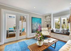 Neutral gray paint color in this living room is calming but the pop of bright blue makes it feel playful as well