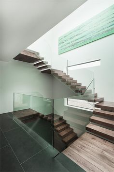 Open riser staircase with thick wood treads end-supported by surrounding wall and glass sheet railing; Abbots Way, Southampton.