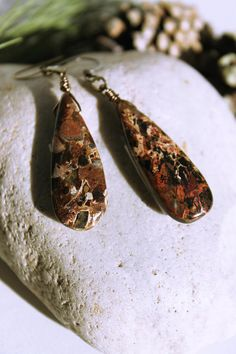 A pair of hand wire wrapped earrings made with large natural Jasper teardrop shape beads. The highly polished stone drops are approximately 13 MM X 35 MM in size........beautiful earth tones that will compliment your wardrobe. Antiqued brass and hues of chocolate brown. The earrings hang