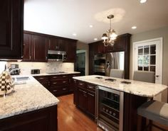White Springs Granite Countertops : Contemporary Kitchen With White Springs Granite Countertop And Kitchen Island With Ceiling Lamps, Hardwood Flooring, And Brown Cabinets
