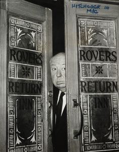 Alfred Hitchcock peering through the doors of the Rovers Return pub in the soap Coronation Street, June 1964 by Joe Darby for the Daily Herald