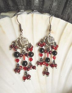 Alluring Victorian Goth Rose Chandelier Earrings! Created with gunmetal rose findings, I added clusters of deep wine potato pearls, red bicone crystals, and onyx beads. Red glass aurora borealis bugle beads are used at each center drop, and gunmetal glass seed beads are used as spacers. Dainty, yet stunning with lots of bling! Gunmetal steel ear wires complete this design. Made with love and care to last!  Light and comfortable.  These earrings measure 2 3/4 in length from the top of the...