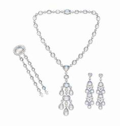 A SET OF MOONSTONE AND DIAMOND JEWELRY Comprising a necklace, designed as a flexible line of bezel-set oval cabochon moonstones, spaced by collet-set rose-cut diamonds, suspending twin girandole moonstone and diamond pendants; a pair of ear pendants and a bracelet with a detachable clasp en suite, mounted in 18k white gold.