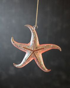 Coral Sand Starfish Ornament, by Enesco. Glitter and tiny gems this glass starfish ornament. This one is a peachy coral pink. Measures 4.5in H x 1in W x 4in L. Made of Glass, Glitter, Gold 14kt, Rope.