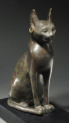 EGYPTIAN BRONZE CAT, THE EMBODIMENT OF THE GODDESS BASTET, Patroness of joy and of women, seated in the traditional attitude. with alert ears and ancient gold earrings. Very fine style. XXVIth Dynasty, 664-525 BC H. 11 in. (27.9 cm.)