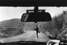 by Josef Koudelka  Boy trying to get lift in car passing from Greece into Albania, 1994.