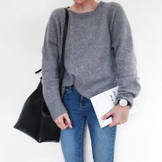 Loose grey pullover tucked in and tight denim with a large face simple watch. Black bag