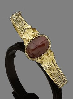 A gold and cornelian archaeological revival hinged bangle, by Melillo, circa 1865 The central cornelian scarab, circa 400 BC, engraved on reverse with a centaur, within a collet of fine granulated pyramid and lotus flower motifs, between shoulders of overlapping ivy leaves and gold berries, on a bangle of delicate powder and circular granulation