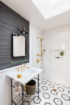 From the subway tile paired with the chic, gray-striped wallpaper to the minimal sink featuring striking gold hardware, every detail of this bathroom is perfection. Grey Striped Wallpaper, Bathroom Lighting Design, Design Bathroom, Penny Tile, Bathroom Wallpaper, Tile Patterns, Bathroom Inspiration, Elle Decor, Vanity