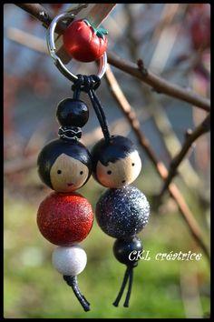Porte-clés poupées mariés rouge et gris anthracite pailleté.  Peut aussi être utilisé en bijoux de sac à main.  Les perles en bois sont peintes et vernies à la main.  Perles bois têtes cheveux noirs (18mm), perles bois corps rouge pailleté/gris anthracite pailleté (18mm), perles bois du bas blanc pailleté/noir (12mm).  Hauteur poupées 6 cm, hauteur total avec porte-clés 10 cm.  Fait main.  Ils sont livrés dans une jolie petite boîte.