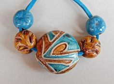 The set consists of =1 bead-lentil stoneware , handcarved ,It has the same design on both sides ,this bead are hollow and weigh very little , have ocher and turquoise glazes , measures 30 x 30 mm. - 4 beads hand-carved ,have ocher and turquoise glazes . By Mª Carmen Rodriguez Martinez ( Majoyoal ) https://www.facebook.com/groups/CeramicArtBeadMarket