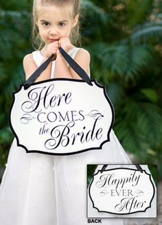 "How do you begin a fairy tale wedding? With this sign displayed before and after your ceremony! This white, crest-shaped sign is printed on two sides. The front displays ""Here Comes the Bride"" and ""Happily Ever After"" on the reverse side in black. Features and Facts:  Measures:  14"" W x 10"" H.  7/8"" black satin ribbon included.  Material:  Foam-core poster board.  Customer assembly required."