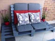 canapé en palette de bois peint en bleu avec des coussins à motif floral