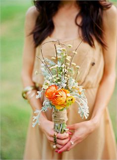 rustic wedding bouquet.  I like the burlap wrap and the brown stick things, still wondering about the flowers