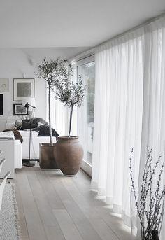 バルコニーに続く大きなガラスのドアも清潔感の溢れるカーテンで。自然な光を通し明るいリビングを作ります。