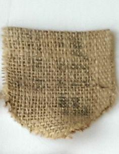 Een vlaggetje van jute. Het jute is afkomstig van hergebruikte koffiezakken. De randen zijn gestikt om rafelen verder te voorkomen.