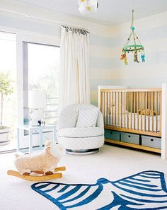 Stylishly modern, light and bright, nursery {with a very cool swivel chair}..love the chair