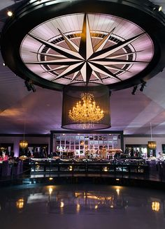 A crystal chandelier behind a black screen hangs above a sunken dance floor.
