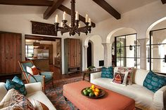 Soft peach and teal tones accent a cream color story in this Spanish-style living room. #DreamBuilders